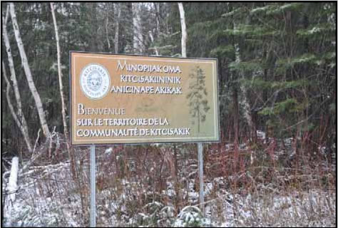 Photogragh of a sign welcoming visitors into the Kitcisakik community. Sign written in both French and Algonquin.