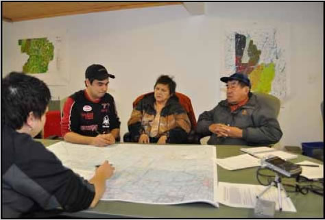 Photograph of a group of elders discussing around a map.