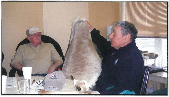 Photograph of an elder holding up his caribou skin at the workshop.